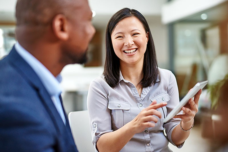 Smiling business professional on tablet computer with client