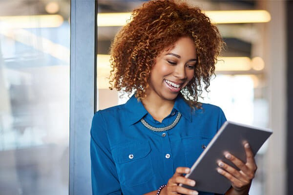 Smiling businesswoman uses tablet device