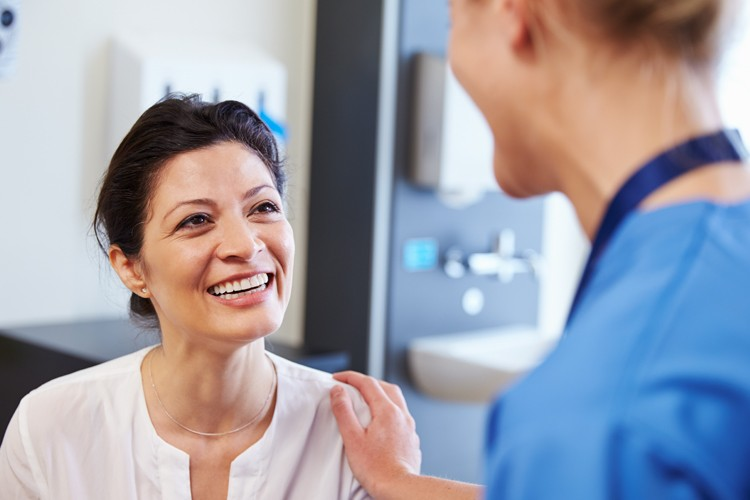 Nurse shares healthcare information with smiling patient in hospital
