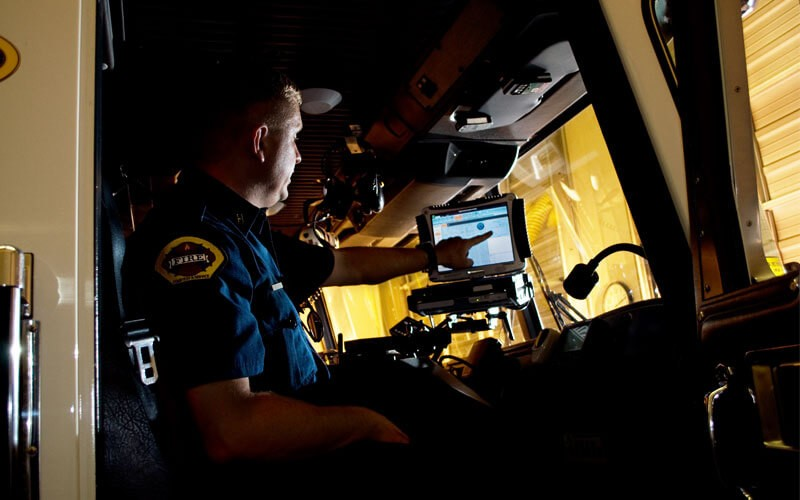 Firefighter in truck with technology. Purchase state and local government contracts, OMNI partners, NASPO, National Association of State Procurement contracts