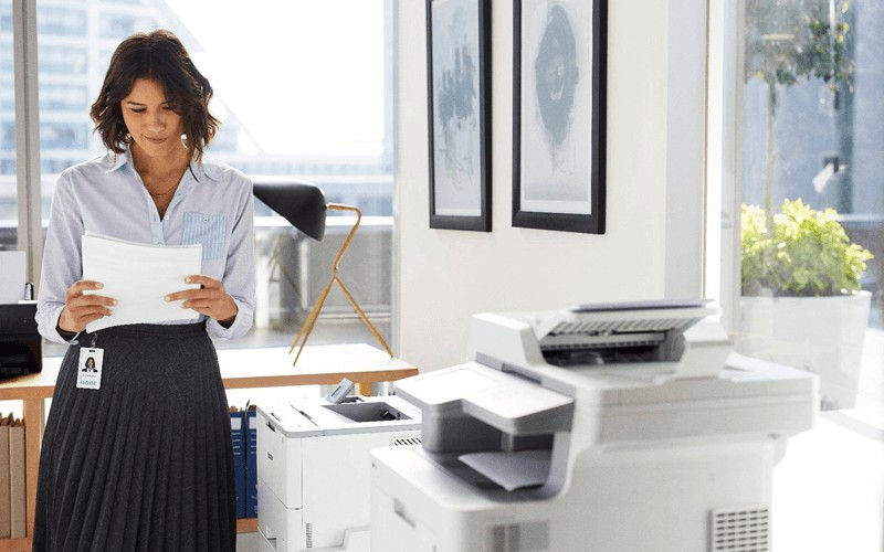 Woman using Brother printer with government badge