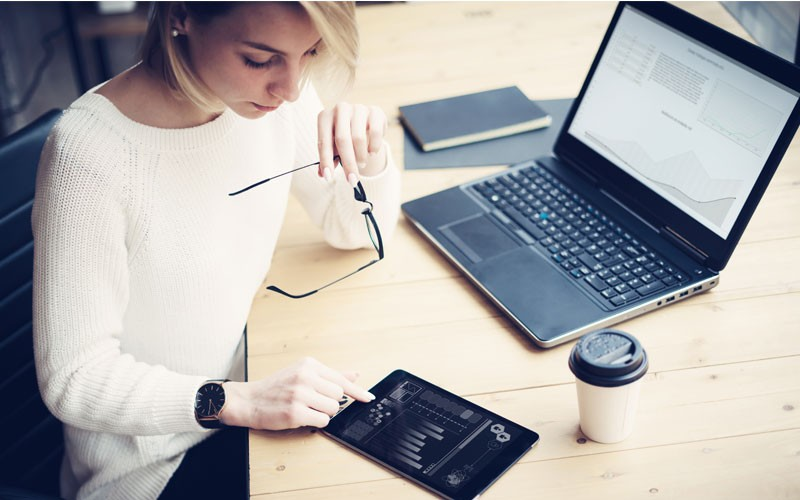 Woman using laptop and tablet device management software