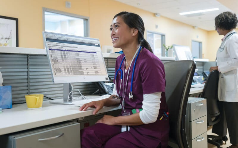 Nurse sitting at nurses station with HP devices on desk