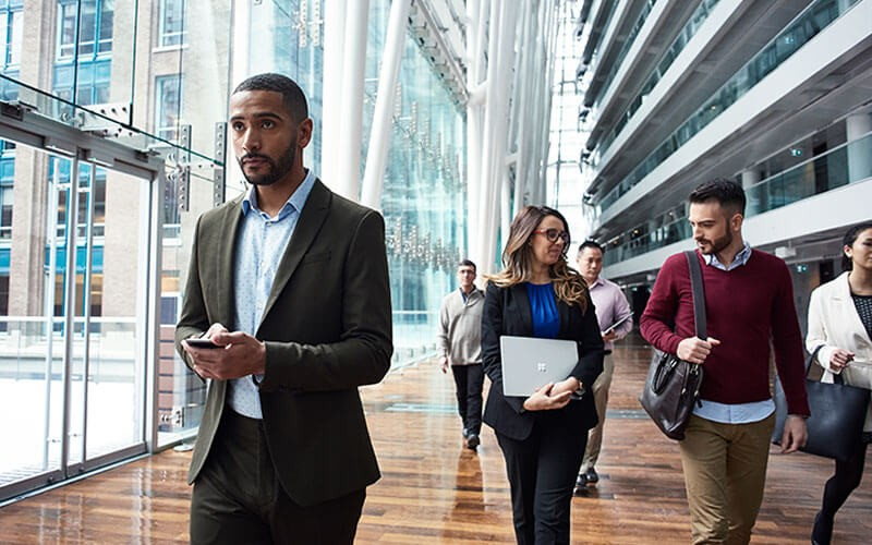Business professionals walking through building with Microsoft devices