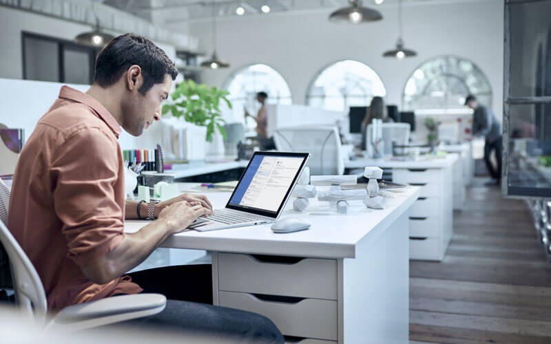User working on Surface in open office