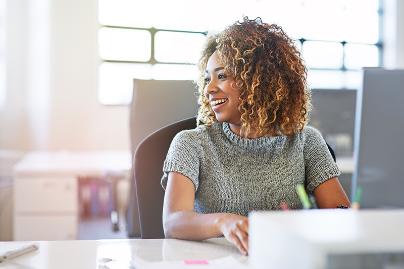Business professional smiling to colleague while at her desk in office