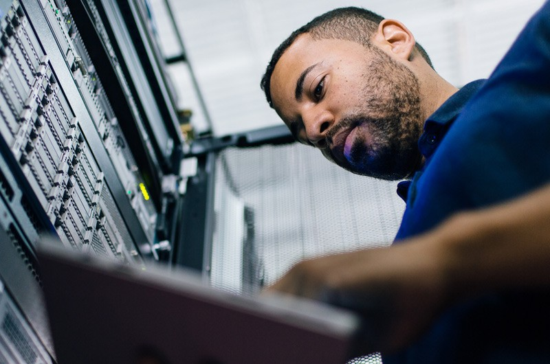 Man working on a tablet in a server room
