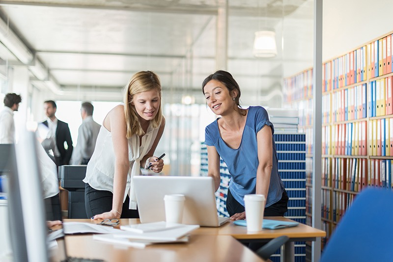 Focus on two women standing in front of a laptop in a modern office looking at customer data