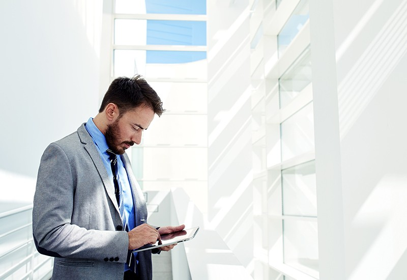 Businessman checking email on tablet computer in office hallway