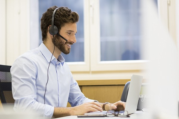 smiling business man using headset and laptop