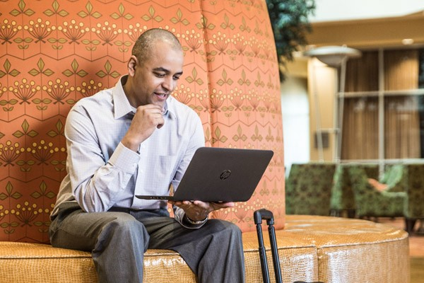 businessman using laptop video while traveling