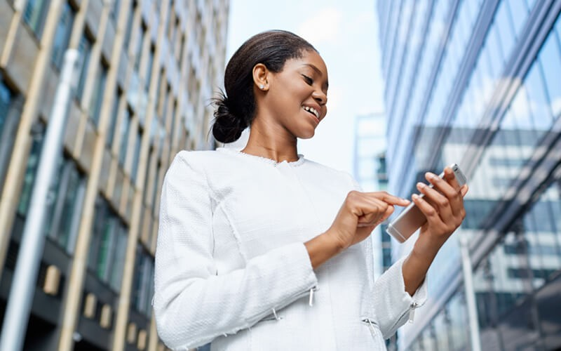 Businesswoman working outside on mobile device