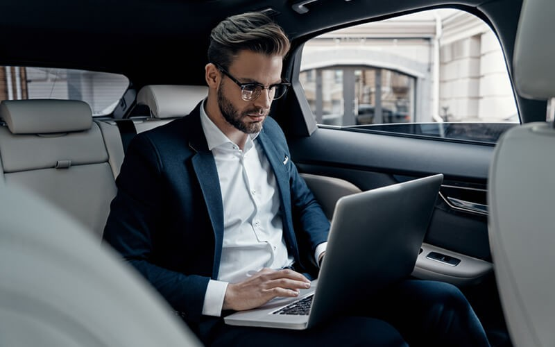 Government official working from laptop in car